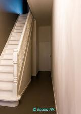 Gesloten rechte trap met klassiek draaiwerk. Bloktrede aan het vertrek.