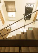 Zicht naar beneden vanop de overloop. Ruime inkomhal waarin deze trap mooi tot zijn recht komt.